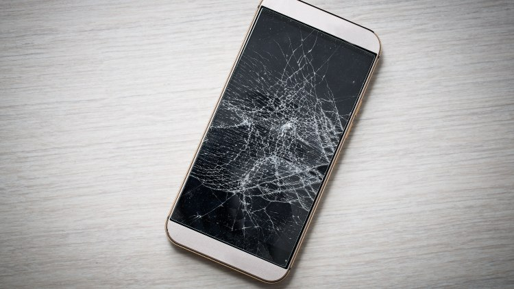 Modern broken mobile phone on wooden background.; Shutterstock ID 357287024