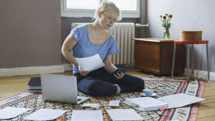 Young woman doing paperwork while sitting at home