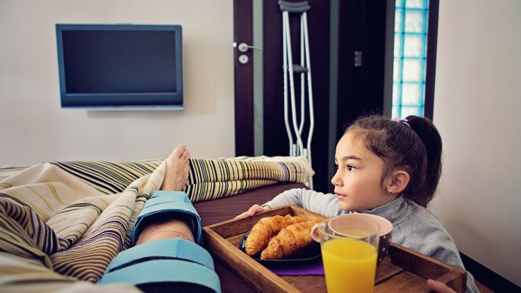 Little girl is helping her father who is lying in the bed after knee surgery bringing him breakfast in bed.