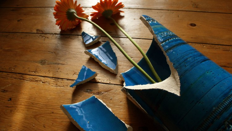 A broken vase with flowers.